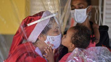 Une photo prise à Noël au Brésil, entre une volontaire et une enfant précarisée séparée par un rideau en plastique, coronavirus oblige.