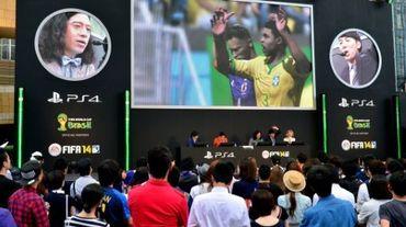 Des fans assistent, sur un écran géant, à un match de foot sur PlayStation à Tokyo, le 4 juin 2014
