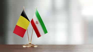 Belgian And Iranian Flag Pair On A Desk Over Defocused Background