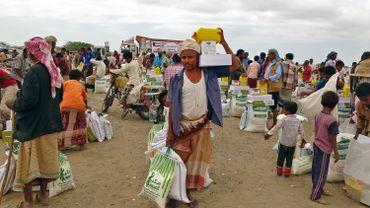Des personnes déplacées à cause des conflits reçoivent une aide alimentaire offerte par une organisation caritative koweïtienne dans le village de Hays, près de la zone de conflit dans la province de Hodeida, à l'ouest du Yémen, le 22 février 2021.