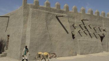Un homme passe avec deux ânes devant la mosquée en argile de Tombouctou