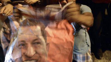 Un partisan d'Hugo Chavez brandit son portrait à l'extérieur de l'hôpital de Caracas