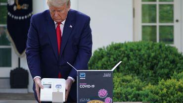 Donald Trump tient dans ses mains un test des laboratoires Abbott censé donner des résultats en 5 minutes, ce 30 mars à la Maison-Blanche
