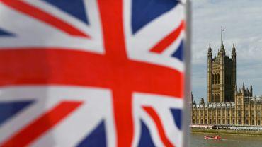 Le Parlement britannique vu depuis le pont de Westminster avec un drapeau britannique à l'avant plan, à Londres le 28 août 2019