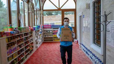 Abdulsamet Cakir, imam de la mosquée Dedeman à Istanbul, porte des cartons de vivres le 21 avril 2020 dans l'entrée de la mosquée