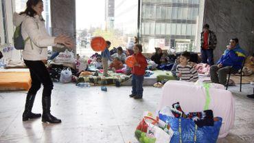 Une femme joue avec les enfants de familles sans abris installées dans les couloirs de la gare du Nord à Bruxelles