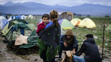 Une femme porte un enfant dans un camp de réfugiés à la frontière entre la Grèce et la Macédoine, le 9 mars 2016.