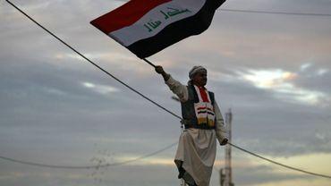 Photo prise le 10 décembre 2017 montrant un Irakien brandissant le drapeau national sur la place Tahrir à Bagdad lors d'une cérémonie célébrant la victoire sur les jihadistes