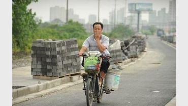 Un habitant se masque le nez pour éviter de respirer les émanations d'une énorme décharge d'ordures, le 7 juillet 2012 à Songjiang, un arrondissement de Shanghai