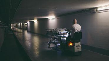 Emmené par un brancardier de l'unité Covid-19 où il est décédé, un patient effectue son dernier voyage jusqu'à la morgue (format original en fin d'article).