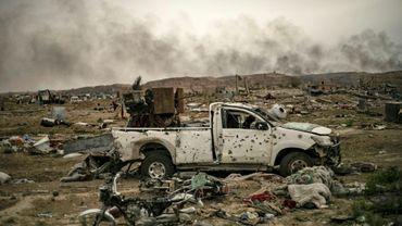 """Au lendemain de la chute du """"califat"""" du groupe jihadiste Etat islamique (EI) en Syrie, de la fumée noire s'élève au-dessus du village syrien de Baghouz (est) où des voitures ont été calcinées et des bâtiments endommagés, le 24 mars 2019"""