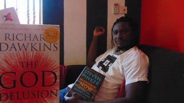 Michael Osei Assibey, au milieu de certains livres de sa bibliothèque, dont des ouvrages de Richard Dawkins