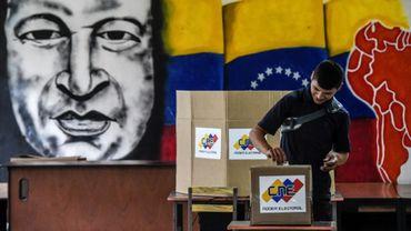 Un homme vote devant une fresque de l'ancien président vénézuélien Hugo Chavez, à Caracas le 20 mai 2018