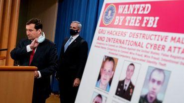 Une affiche des six agents russes recherchés par les Etats-Unis pour leur rôle supposé dans une série d'attaques informatiques, le 19 octobre 2020 à Washington lors d'une conférence de presse du ministre adjoint de la justice John Demers (g)