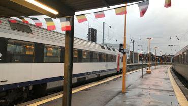 En gare de Maubeuge, des drapeaux belges et français accueillent les voyageurs.