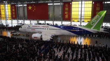 L'avion long de 39 mètres, de couleur blanche avec un aileron vert, est sorti d'un gigantesque hangar décoré aux couleurs du drapeau chinois pour être présenté devant un public.
