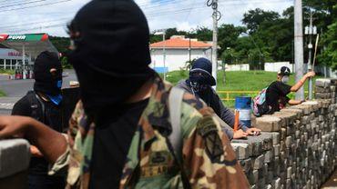 Des étudiants munis d'armes artisanales derrière une barricade, le 23 juin 2018 à Managua, au Nicaragua