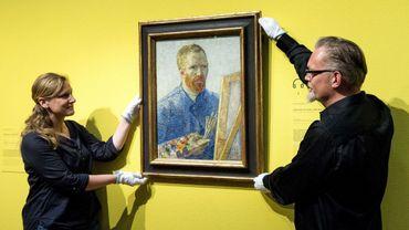 Des employés du Musée Van Gogh rénové accrochent l'autoportrait du peintre, réalisé en 1888