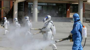 Des bénévoles désinfectent la cour d'une école avant sa réouverture, le 12 avril 2020 à Weifand, dans l'est de la Chine