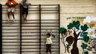 Des enfants jouent dans une cour d'école abandonnée où sont accueillis des réfugiés afghans et syriens, à Athènes le 1er juillet 2016