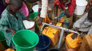 Des femmes et des enfants du camp de déplacés de Muna, à la périphérie de la grande ville de Maiduguri, capitale de l'État du Borno, au Nigeria, collectent de l'eau d'un puits le 30 juin 2016