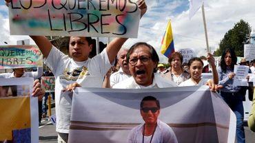 Galo Ortega (à droite) avec une photo de son fils, le journaliste Javier Ortega, pendant une manifestation pour sa libération le 1er avril 2018 à Quito.