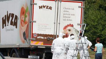 Des agents de la police scientifique devant un camion où ont été retrouvés les corps de 71 migrants morts asphyxiés, près de Neusiedl am See (Autriche), le 27 août 2015