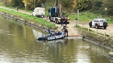 Un zodiac navigue sur le canal avec à son bord un ou deux plongeurs accompagnés de policiers.
