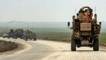 Un véhicule d'un convoi militaire américain roule derrière un convoi russe sur l'autoroute M4 dans la province de Hassaké dans le nord-est de la Syrie, le 20 janvier 2020