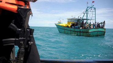 Un policier indonésien surveille des migrants du Sri Lanka qui voulaient aller en Australie mais sont restés bloqués par une panne au large de Banda Aceh en Indonésie, le 13 juin 2016
