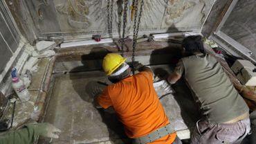 Des experts grecs replacent le couvercle de la tombe.