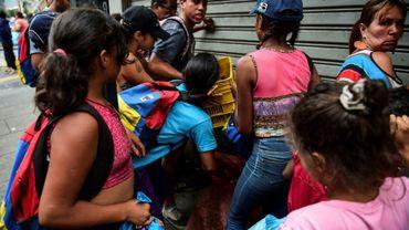 Des gens se battent pour récupérer de la nourriture sur le sol d'un marché de rue à Caracas, le 10 mars 2019