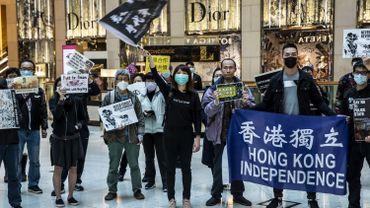 Des employés de bureau et des manifestants se rassemblent lors d'une manifestation pro-démocratie dans un centre commercial du district central de Hong Kong le 21 février 2020