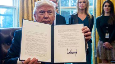 Le président Donald Trump montre l'un des décrets qu'il vient de signer, le 24 janvier 2017 dans le Bureau Ovale de la Maison Blanche, à Washington