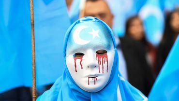 Une personne manifeste contre la persécution des personnes de l'ethnie Ouïghours en Chine.
