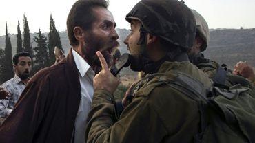 Un palestinien et un soldat israélien se dispute après la décision des autorités israéliennes de fermer une école palestinienne dans la ville d'as-Sawiyah, au sud de Naplouse, le 15 octobre 2018