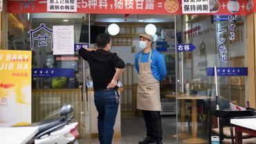 Des employés d'un restaurant munis de masques de protection contre le coronavirus attendent le client à Huanggang, dans la province chinoise du Hubei, le 26 mars 2020