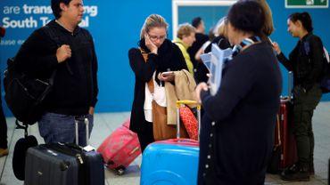 Des employés de Thomas Cook discutent avec des passagers affectés par la faillite du groupe à l'aéroport de Londres-Gatwick le 23 Septembre 2019