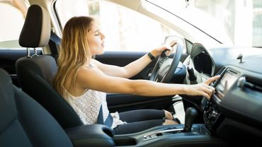 Female driver switching radio stations