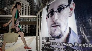 Une femme marche devant une affiche de soutien à Edward Snowden, le 18 juin 2013 à Hong Kong