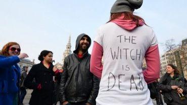 """Une femme portant un t-shirt avec l'inscription """"La sorcière est morte"""", à Londres, le 8 avril 2013"""