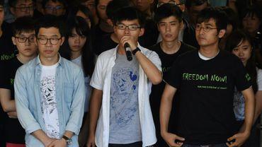Les trois leaders du vaste prodémocratie Joshua Wong (c), Nathan Law (g) et Alex Chow (d) s'adressent aux médias avant le verdict au tribunal de Hong Kong, le 17 août 2017