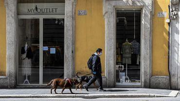 Un homme portant un masque facial promène ses chiens sur une principale rue commerçante déserte de la Via del Corso, le 31 mars 2020, dans le centre de Rome.