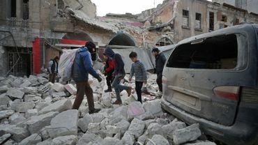 Des Syriens marchent au milieu des décombres d'un bâtiment à la suite d'une frappe aérienne du régime sur la ville d'Idleb dans le nord-ouest de la Syrie le 15 janvier 2020