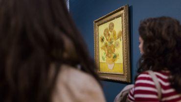 """Des visiteurs regardent le peinture """"Les Tournesols"""" de Vincent van Gogh (1853-1890) au Musée Van Gogh à Amsterdam"""
