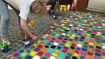 Des pavés colorés peints par des volontaires et par des passants
