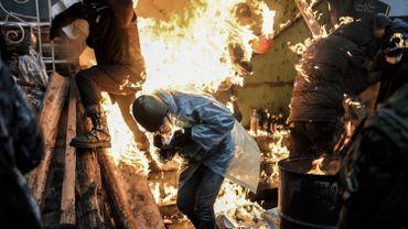 Des manifestants derrière les barricades en feu à Kiev, ce jeudi