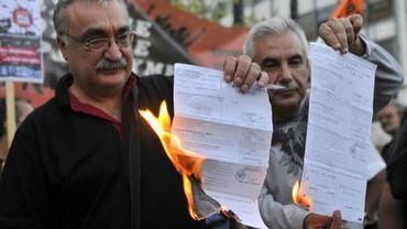 """Des membres du mouvement """"Je ne paie pas"""" brûlent leurs feuilles d'impôts le 22 septembre 2011 à Athènes"""