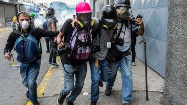 Des journalistes aident un  collègue blessé lors d'une manifestation à Caracas