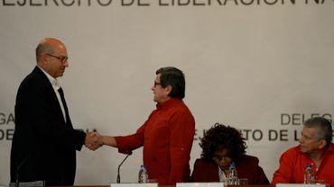 Le représentant de la guérilla de l'ELN Pablo Beltran (d) serre la main du représentant du gouvernement colombien, Mauricio Rodriguez (g), lors d'une rencontre au ministère des Affaires étrangères vénézuélien, le 10 octobre 2016 à Caracas